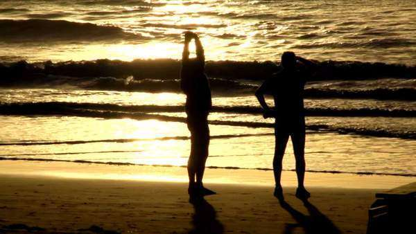 Static shot showing people enjoying time on the beach at sunset Rights-managed stock video
