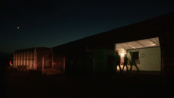 Wide shot of farmers leaving the barn at night Rights-managed stock video