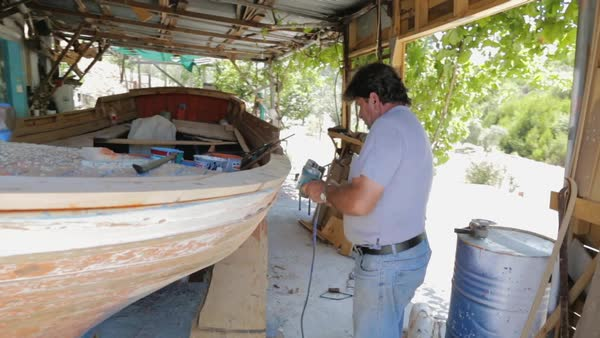 Medium shot of shipwright polishing a boat Rights-managed stock video