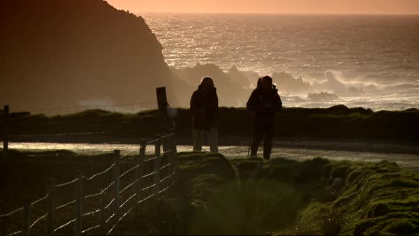 Wide shot of men hiking on a coast Rights-managed stock video