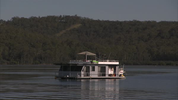 Wide shot of a houseboat on a river Rights-managed stock video
