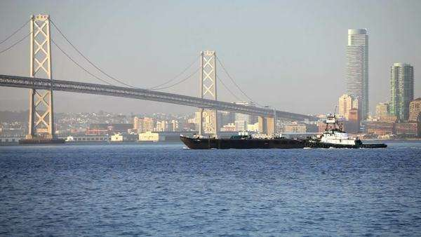 Oakland Bay Bridge with a ship and tugboat crossing the bay Royalty-free stock video