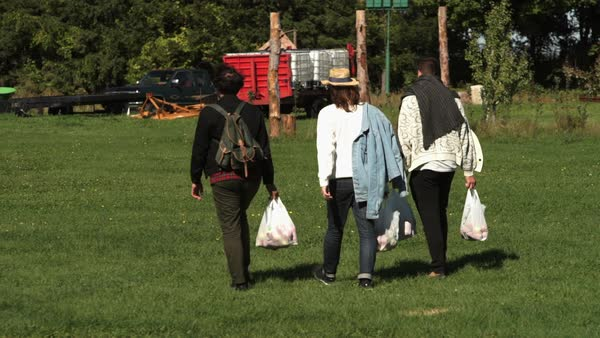 Wide shot of three people walking with plastic bags Royalty-free stock video