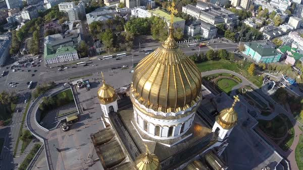 Flight around Cathedral of Christ the Saviour against background of city road and buildings Close up golden dome and cross Moscow Russia Royalty-free stock video