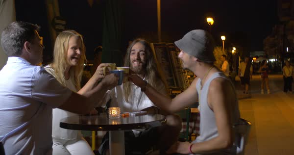 Cheerful group of friends sitting in the evening in the street cafe Royalty-free stock video
