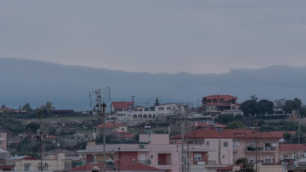 Timelapse in Nea Kallikratia, Greece at sunset seen roofs of houses with antennas and mount Olympus, passing clouds and then night comes and seen light of houses Royalty-free stock video