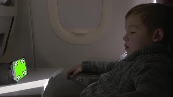 Boy spending flight time with smart phone watching Royalty-free stock video