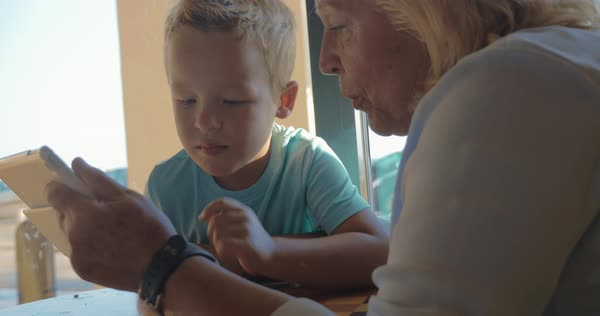 At table at cafe in city of Perea, Greece sits a grandmother with her grandson and teaches him how use tablet Royalty-free stock video