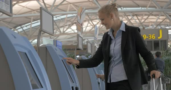 Young woman with passport using self-service machine at the airport to check-in or buy ticket Royalty-free stock video