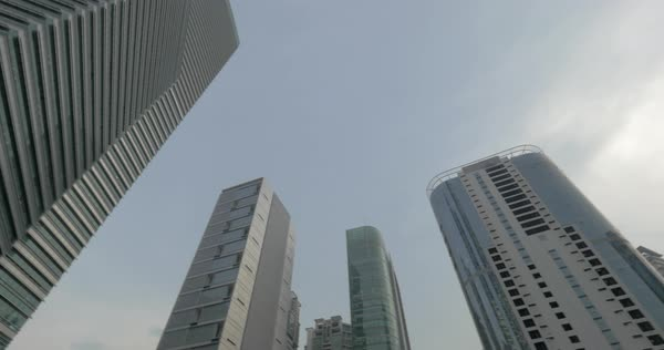 Low angle shot of city skyscrapers with following view of building cranes and construction site Royalty-free stock video