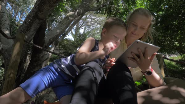 Steadicam shot of mother and child entertaining with tablet computer while relaxing on cushions on wooden deck under the trees Royalty-free stock video