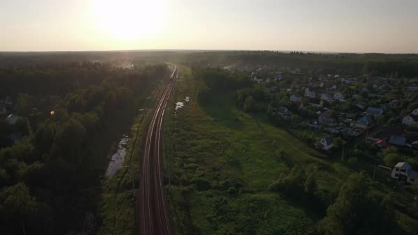 Aerial shot of a cargo train traveling through the green countryside with summer houses. Sunset scene, Russia Royalty-free stock video