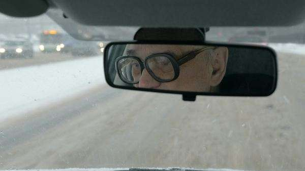 Old man in glasses driving a car. Nasty snowy day and messy roads in the city. Sometimes he looking in the rear mirror Royalty-free stock video