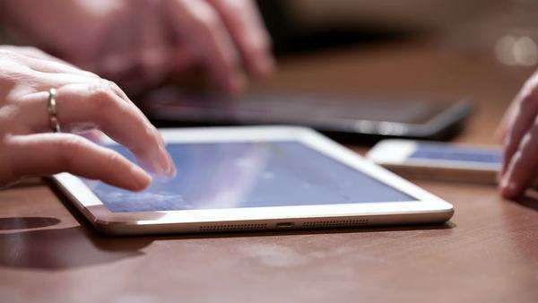 Three people using touchscreen devices. Close-up of hands typing on two tablets and a smartphone Royalty-free stock video