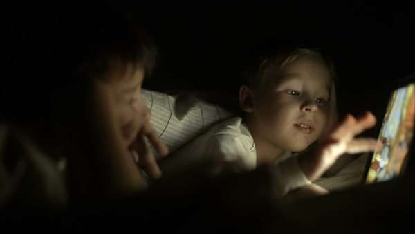 Two boys using tablet lying in bed at night. Bright screen illuminating their faces Royalty-free stock video
