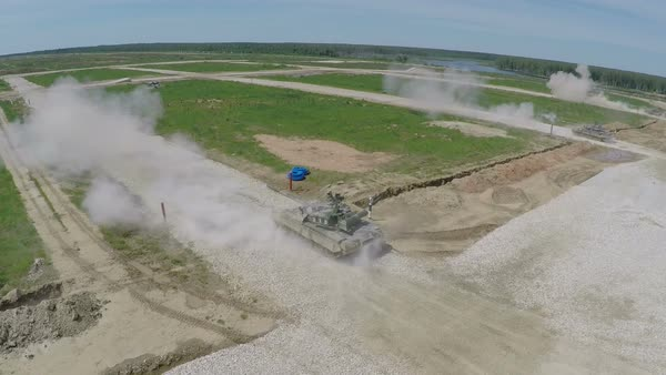 Flying over the two military tanks engaging targets on shooting are during land-forces maneuvers Royalty-free stock video