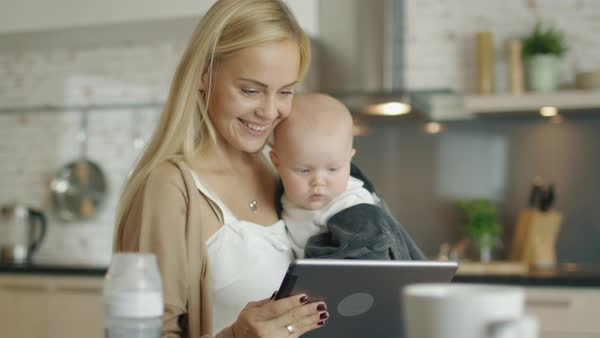 Mother and her baby use tablet computer while being in the kitchen Royalty-free stock video