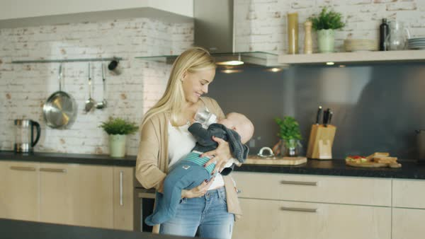 Beautiful blonde mother strolls the kitchen while holding her gorgeous baby Royalty-free stock video