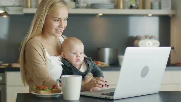 In the kitchen beautiful smiling mother uses laptop while holding adorable child on her knees Royalty-free stock video