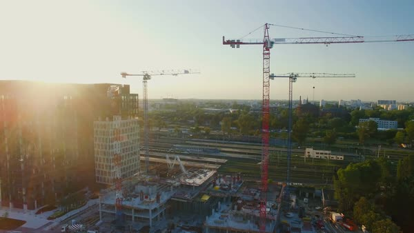 Aerial shot of cranes on a construction site. Great cityscape is visible in sunlight. Royalty-free stock video