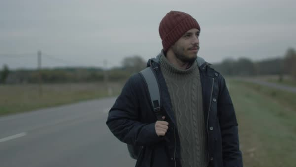 Casualy dressed traveler walking along the highway at a cloudy day. Royalty-free stock video