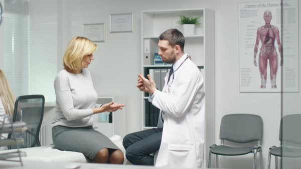 Young Male Doctor Consults His Mid Adult Female Patient. They are Checking Her Hands. Royalty-free stock video