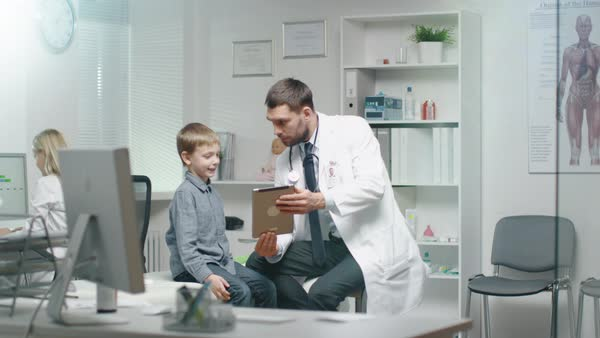 Male Doctor Consults Young Boy by Showing Him Tablet. They Smile and Joke Warmly. Royalty-free stock video