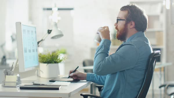 Young bearded man taking notes while working on desktop computer. he sips coffee. he sits in a creatively designed office. Royalty-free stock video