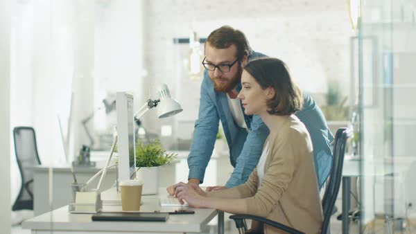 Young man and beautiful woman discuss working issues at workplace. she sits at the table. he stands beside her. she points at something on the screen. Royalty-free stock video