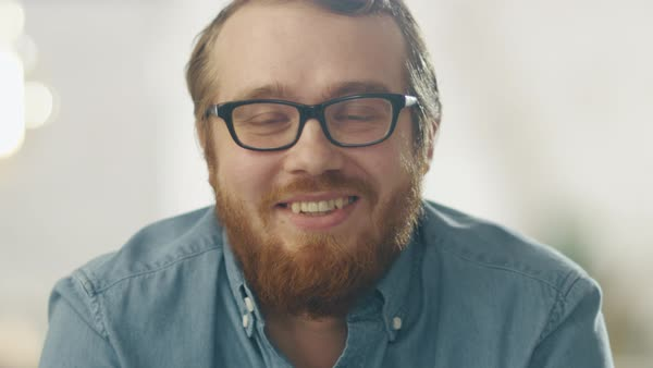 Happy young ginger bearded man wearing glasses smiles into the camera. bright lights in the background. Royalty-free stock video