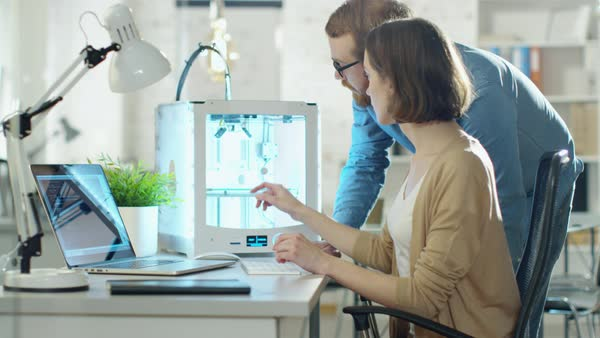 Young man and woman engineers create models using 3d printer. Royalty-free stock video