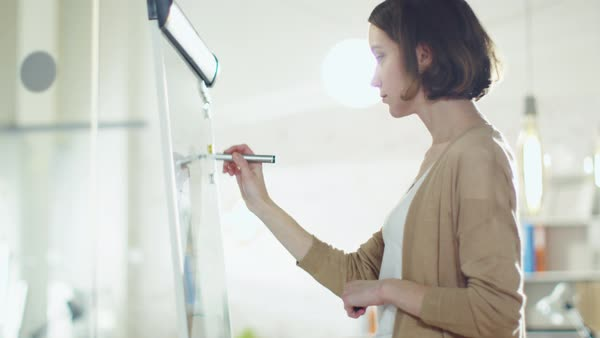 Creative beautiful woman draws on a whiteboard. she stands in a bright lit environment. Royalty-free stock video