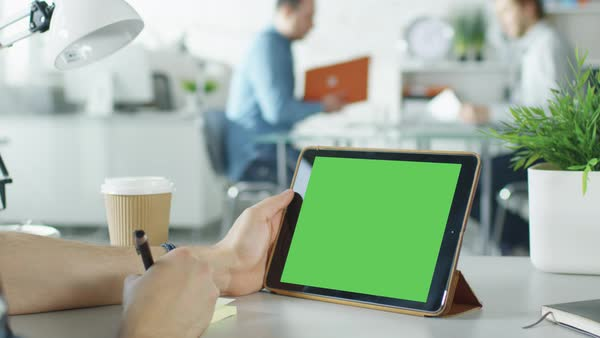 Close-up of a man's hands holding green screen tablet computer and making notes on sticky paper. In the background bright modern office with people working in it. Royalty-free stock video
