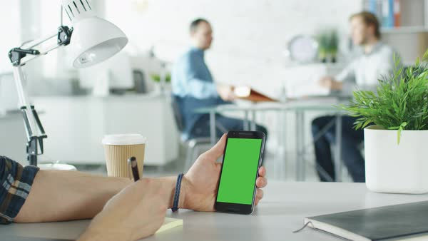 Close-up of a man's hands holding green screen smartphone and making notes with pen on sticky papers. In the background bright modern office with two men shaking hands and starting conversation Royalty-free stock video
