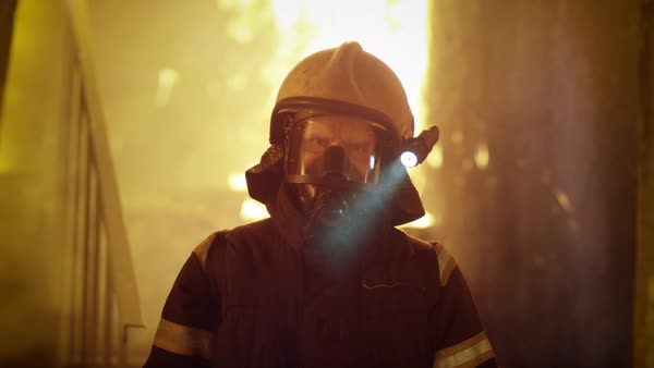 Portrait of a firefighter standing in a burning building Royalty-free stock video