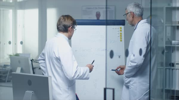 Two specialist doctors discussing health issues and medical drug trial results over whiteboard. Royalty-free stock video