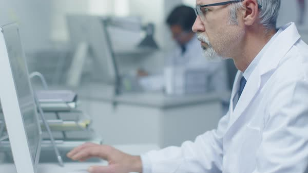 Close-up of medical practitioner typing on a keyboard working on his desktop computer. In background his assistant is working. Royalty-free stock video