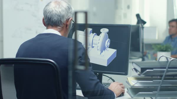 Backview of senior engineer working with 3d model on his personal computer. Also his assistant came in the office and took place at his desk. Royalty-free stock video