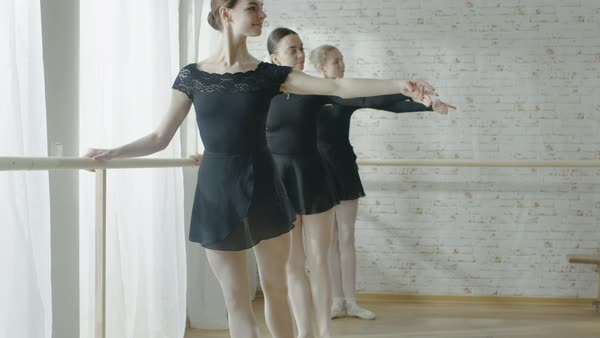 Three young and beautiful ballerinas practicing their dance at the barre Royalty-free stock video
