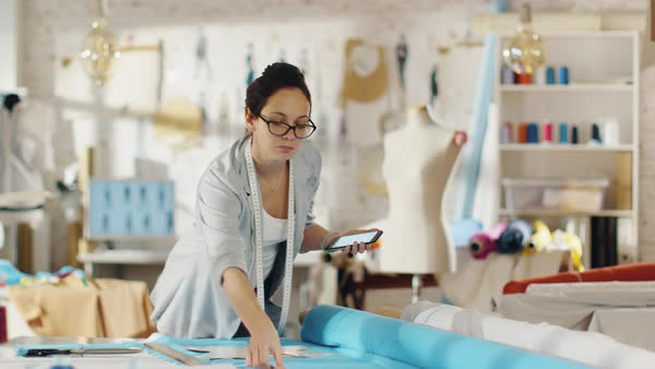 Beautiful brunette fashion designer lays out templates on the fabrics and consults her smartphone. She works in a light colorful studio full of various clothes, fabrics and sketches on the wall. Royalty-free stock video