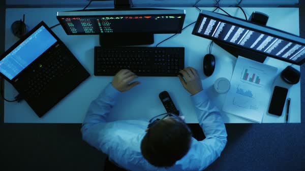 Top view of a stock broker overseeing market's progress. Two monitors and a laptop show him stock's numbers. He's working late at night. Royalty-free stock video