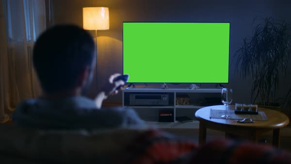 In the evening back view of a middle aged man sitting on a couch watching big flat screen tv, he swtiches channels with remote control Royalty-free stock video