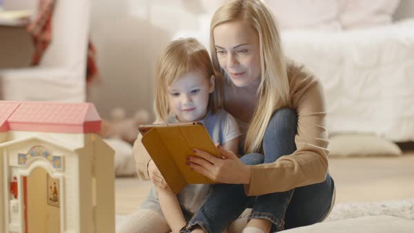 Beautiful mother and her little daughter have good time reading children's books on a tablet computer. Royalty-free stock video