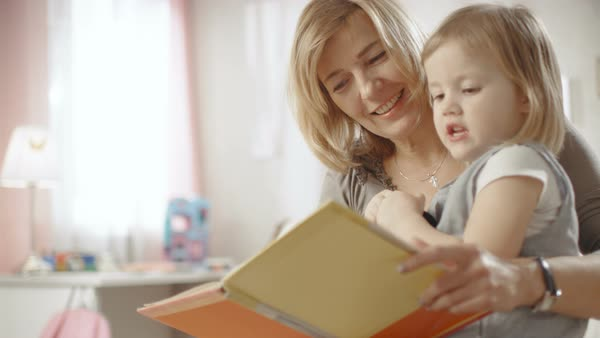 Cute little girl sits on her grandmother's lap and they read children's book. Slow motion. Royalty-free stock video