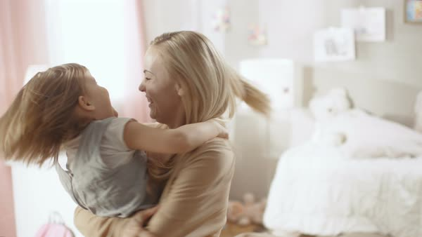 Beautiful happy young mother holds her cute little daughter in her hands and spins with. Both are laughing. Royalty-free stock video