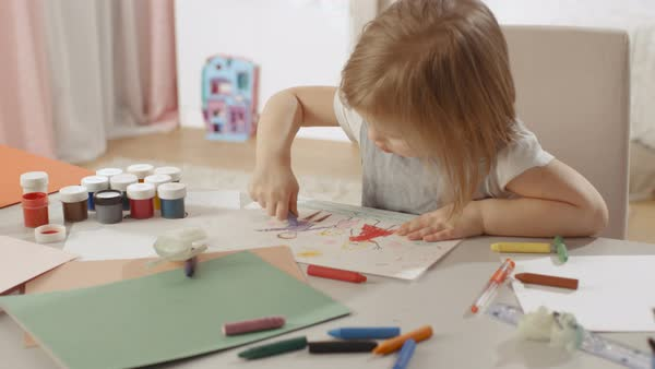 Cute little girl sits at her table and draws with crayons. Her room is pink and cosy. Royalty-free stock video