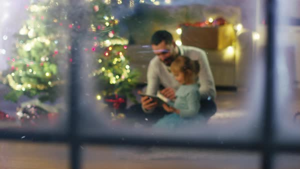 Looking Through Snowy Window. Sitting Under Christmas Tree with Gifts Under It Father Uses Tablet Computer with His Daughter. Royalty-free stock video