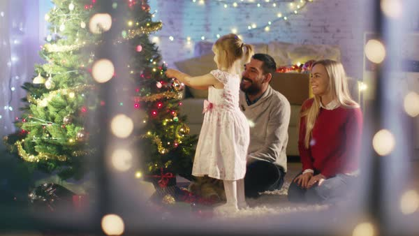 Looking Through Snowy Window. Happy Family: Father, Mother and Their Little Daughter are Decorating Christmas Tree. Royalty-free stock video