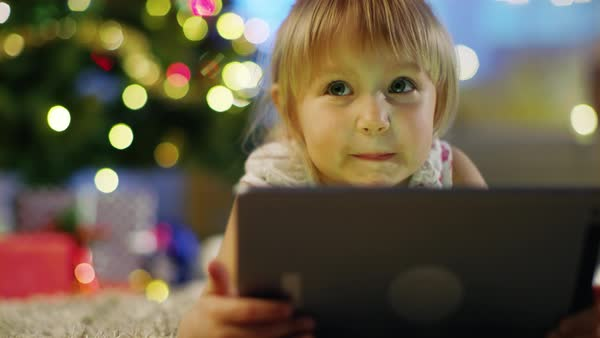 Cute Little Girl With Tablet Computer in Her Hands Lies on the Carpet under the Christmas Tree. Royalty-free stock video