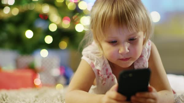 Cute Little Girl With Smartphone in Her Hands Lies on the Carpet under the Christmas Tree. Royalty-free stock video